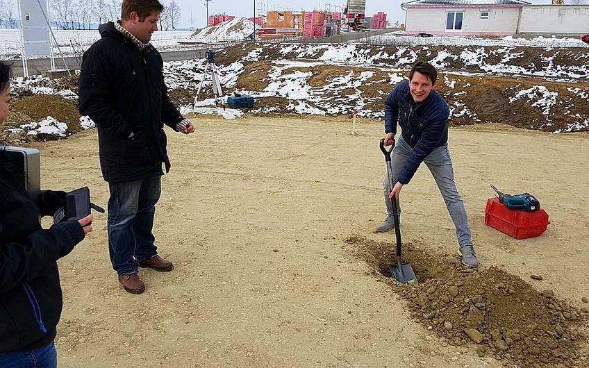 Bauherr mit Spaten beim Ausheben der Grube für den Grundstein.