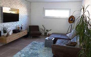 Wohnzimmer der Kern-Haus-Stadtvilla Signus in Otterberg mit Couch, Sideboard und Fernseher
