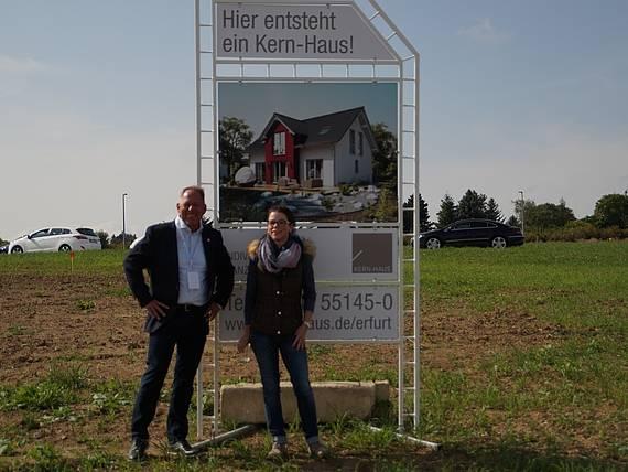 Bauherrin vor Bauschild mit dem Kern-Haus Aura Baugebiet Erfurt-Marbach