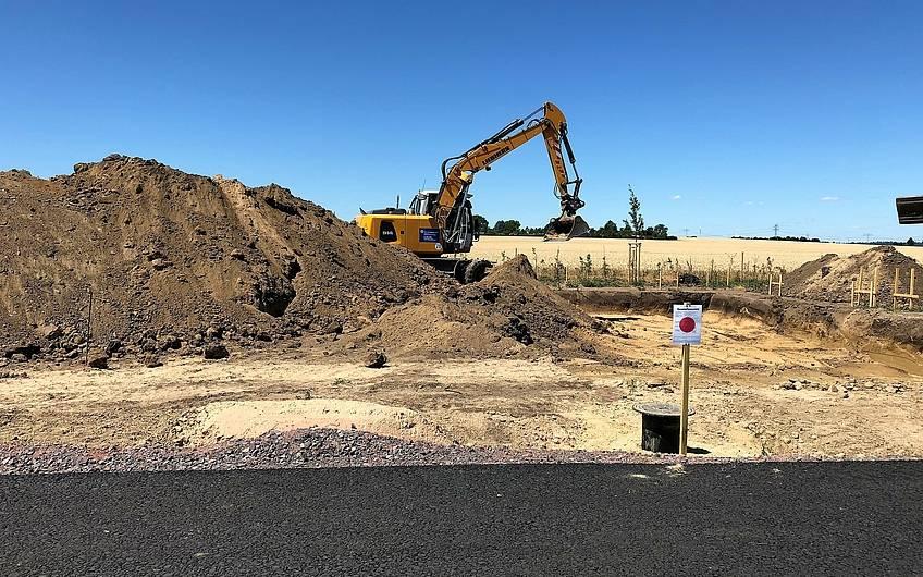 Bagger mit Erdhaufen auf dem Baugebiet in Magdeburg-Diesdorf