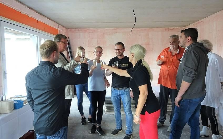 Bauherren stoßen auf ihr künftiges Eigenheim von Kern-Haus an