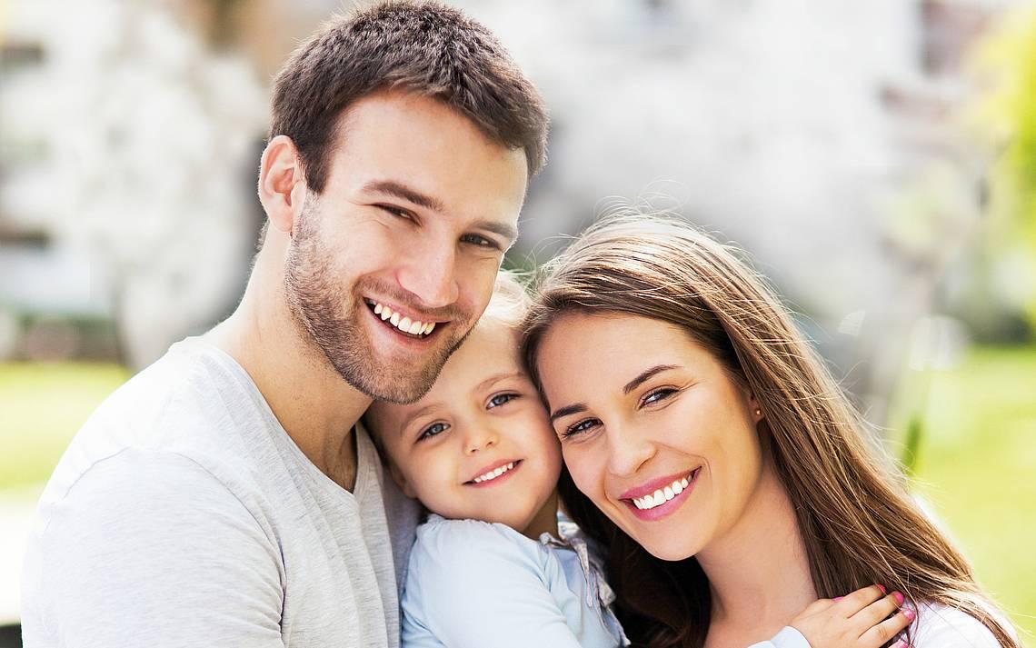 Glückliche Eltern mit Kind auf dem Arm
