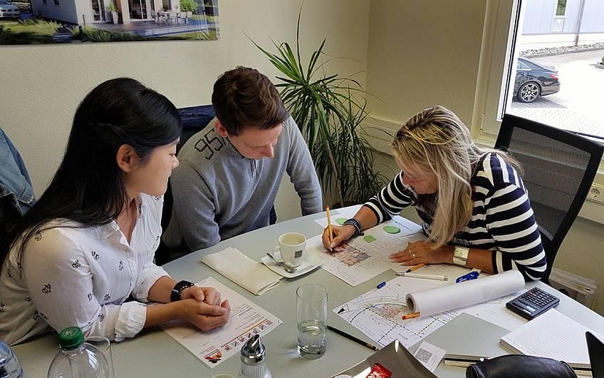 Architektin mit Bauherren am Tisch mit Grundriss.