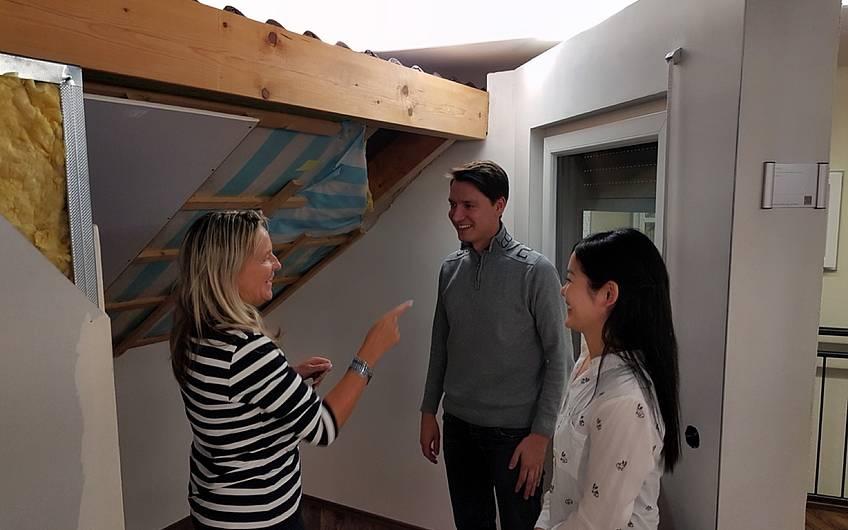 Architektin mit Bauherren vor beispielhaftem Dachaufbau.