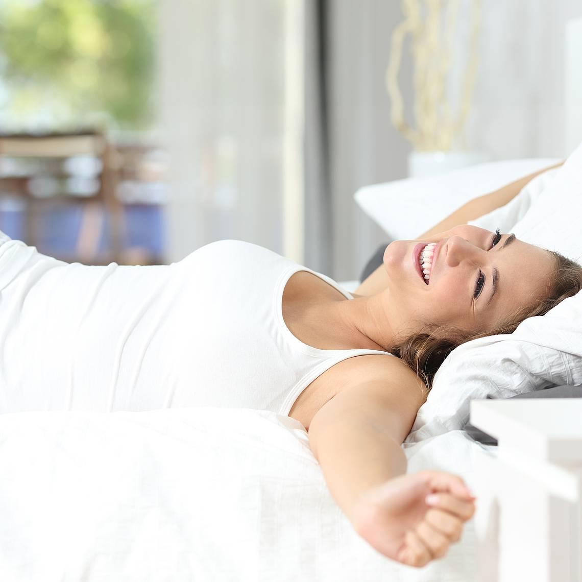 Frau wird wach im Bett