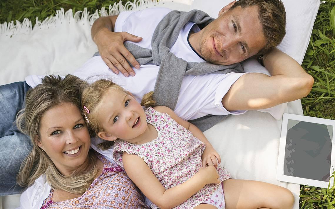 Familie liegt auf Decke