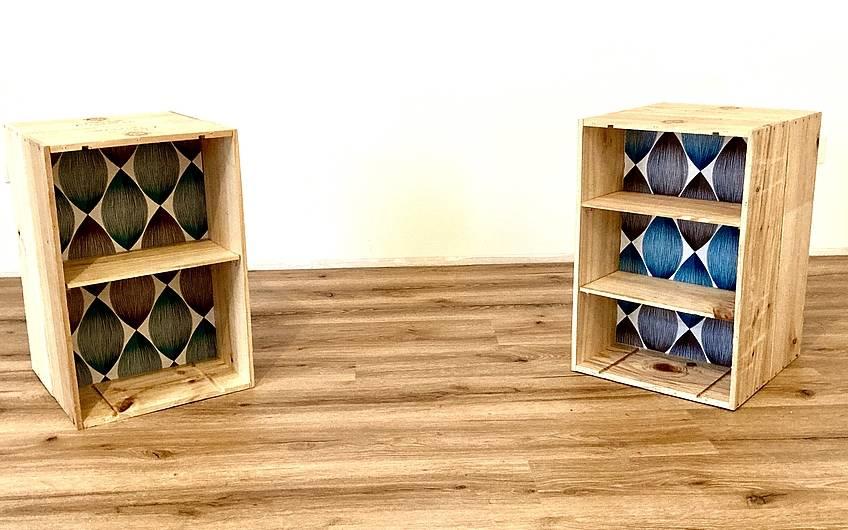 Die Bauherrin hat aus Tapetenresten und alten Champagnerkisten zwei Nachtschränkchen gefertigt, passend zur Wand!