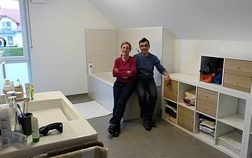 Bauherren sitzen auf der Badewanne im Badezimmer des individuell geplanten Einfamilienhaus Signum von Kern-Haus in Römerberg