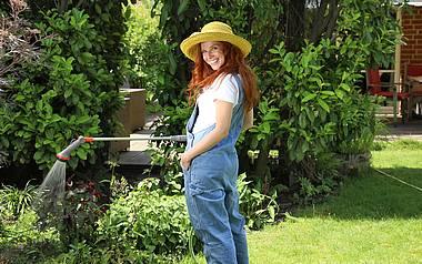 Rothaarige Frau steht im Garten