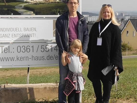 Bauherren vor Bauschild mit dem Kern-Haus Luna Baugebiet Erfurt-Marbach