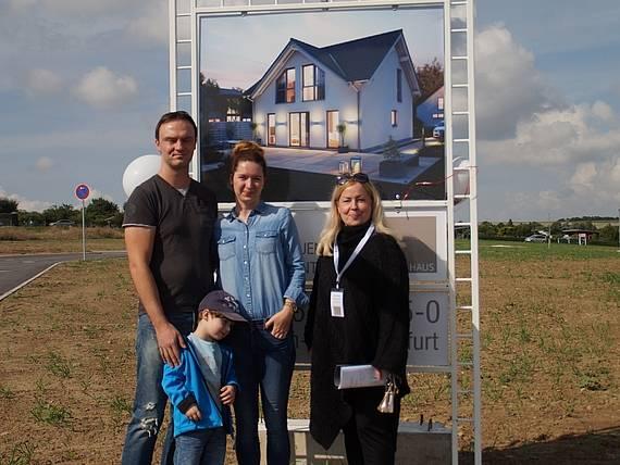 Bauherren vor Bauschild mit dem Kern-Haus Komfort Baugebiet Erfurt-Marbach