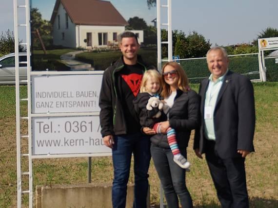 Bauherr vor Bauschild mit dem Kern-Haus Luna Baugebiet Erfurt-Marbach