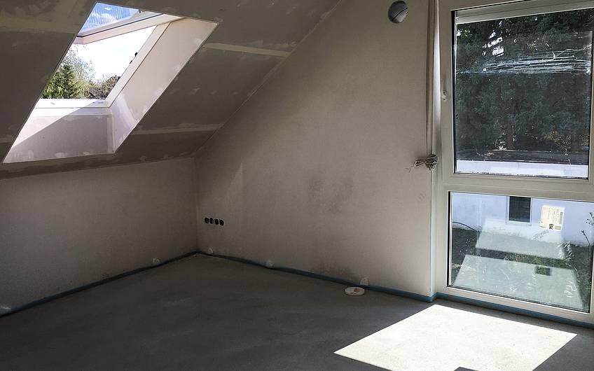 Dachgeschosszimmer mit Dachfenster im Rohbau des Kern-Haus Komfort