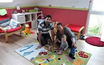 Bauherren mit Tochter im Kinderzimmer des Familienhauses Komfort in Linkenheim-Hochstetten