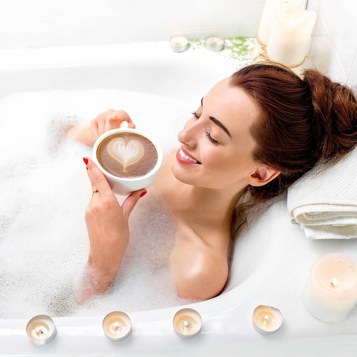 Frau in Badewanne mit Kaffee