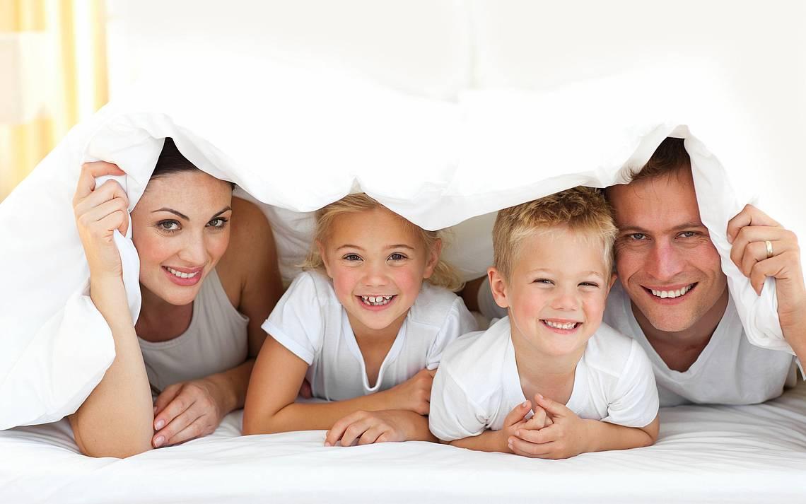 Vierköpfige Familie unter einer Bettdecke