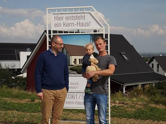 Baugebiet Erfurt Marbach Bauherr vor Bauschild mit dem Kern-Haus Luna