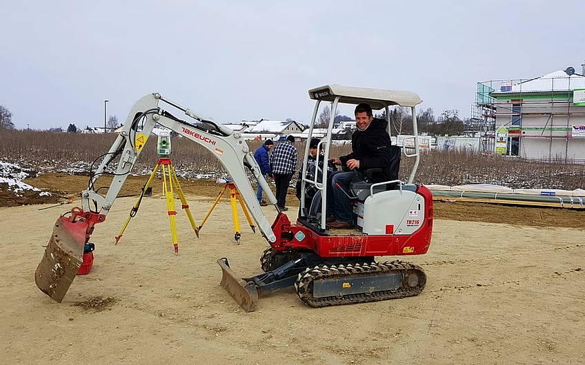 Bauleiter Oliver Marquart im Minibagger beim Öffnen des Bodens mit einer Schaufel