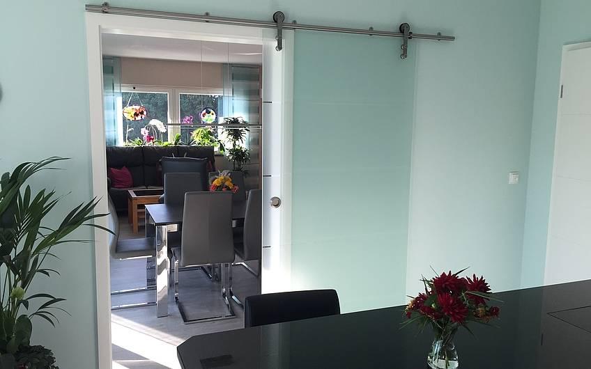 Der Essbereich ist mit einer schicken Glastür zur Küche getrennt.