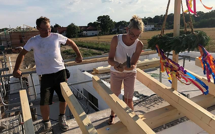 Bauherrin schlägt letzten Nagel in den Dachbalken in Magdeburg
