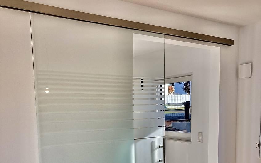qEine elegante Glastür zum Schieben trennt nun bei Bedarf Küche und Wohnzimmer.